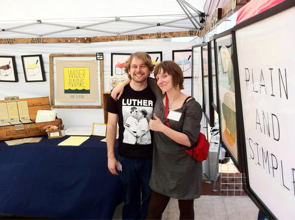 Justin and Courtney stand in a tent showcasing their work.