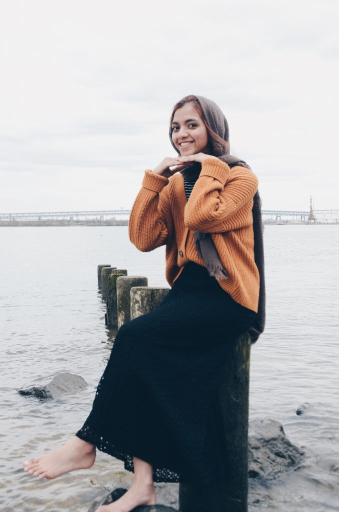 Fahima sitting by the ocean.