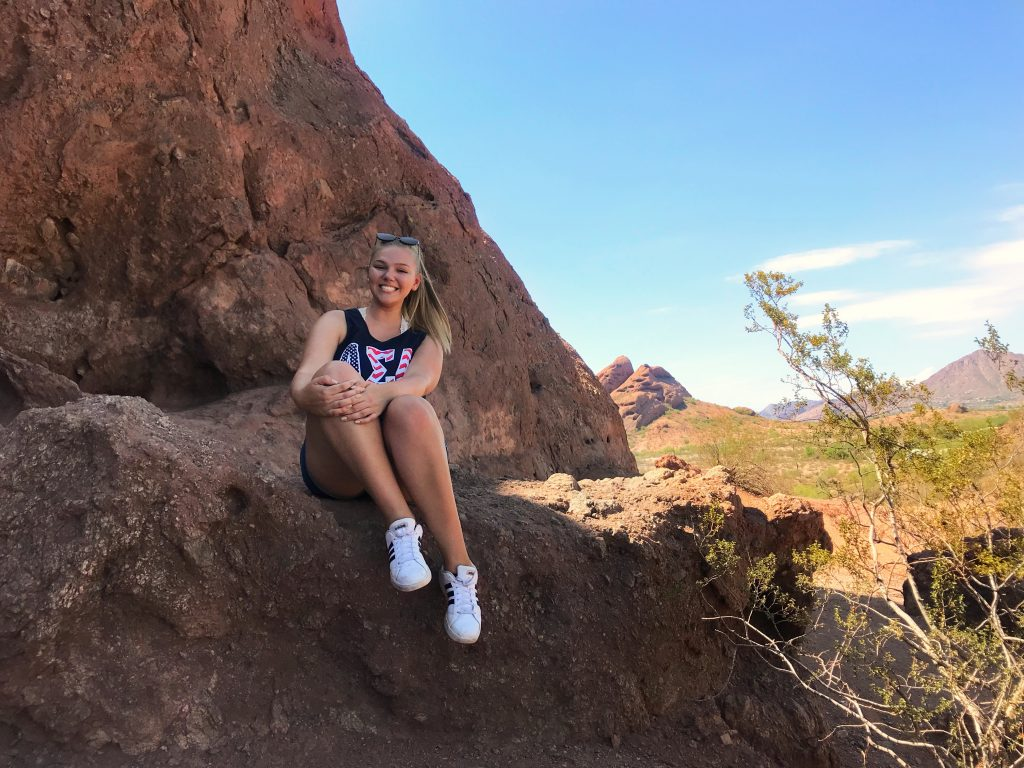 Genna Gaskill hikes in the red mountain region - here she is sitting on a rock with mountains behind her.