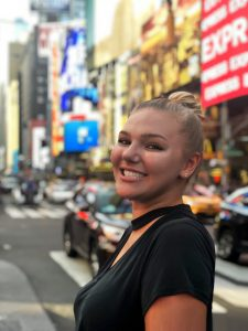 A close-up photo of Genna posing and smiling in front of a busy street in New York City.