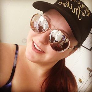 Kimberly poses for a selfie in sunglasses and a baseball cap.