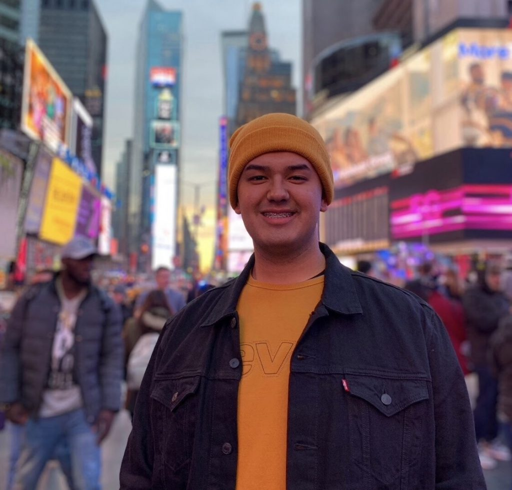 Daniel Marquez standing and smiling on a busy street in New York City.