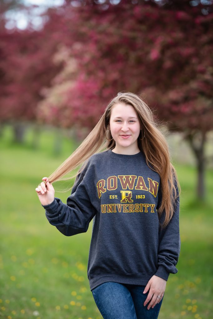 Shayla stands in a grassy field wearing a gray Rowan t-shirt.