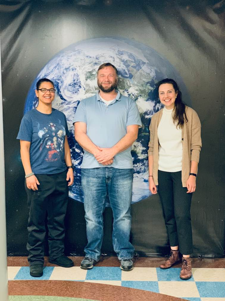 Jonathan and two colleagues stand in front of a black background with the Earth on it.