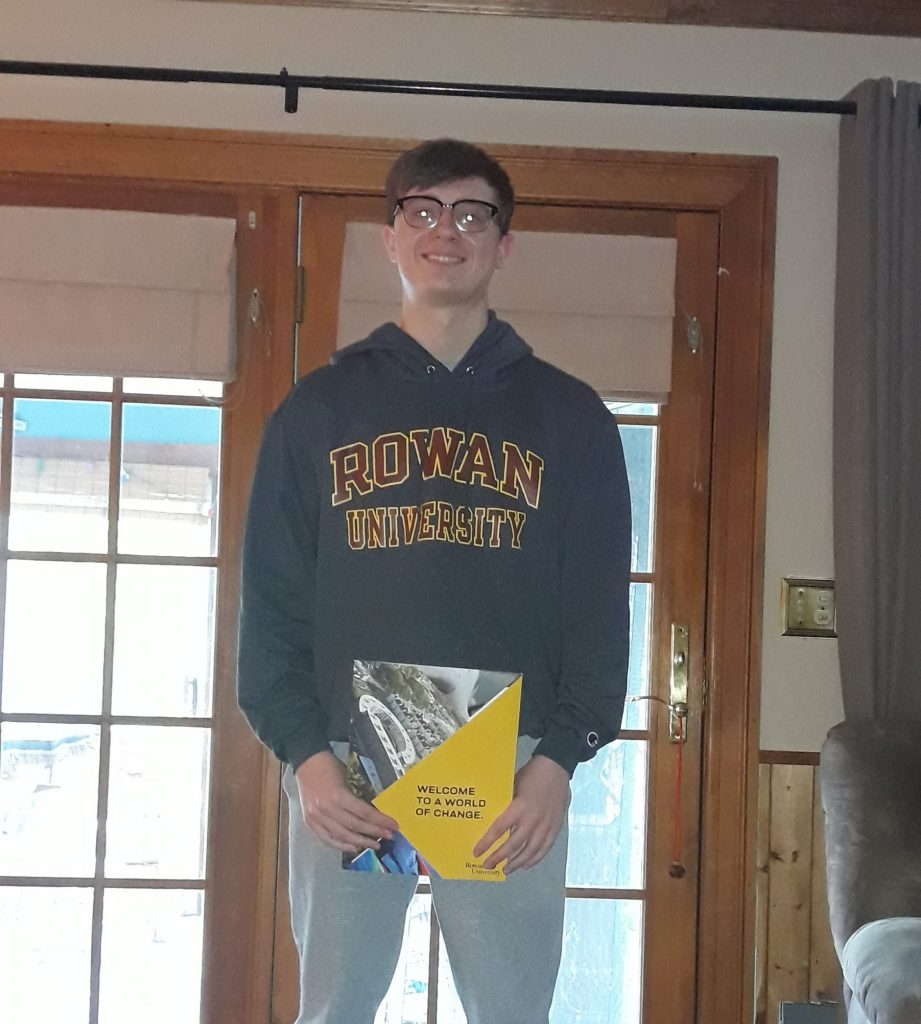 A photo of Alex holding his Rowan admissions package and wearing a gray Rowan sweatshirt.
