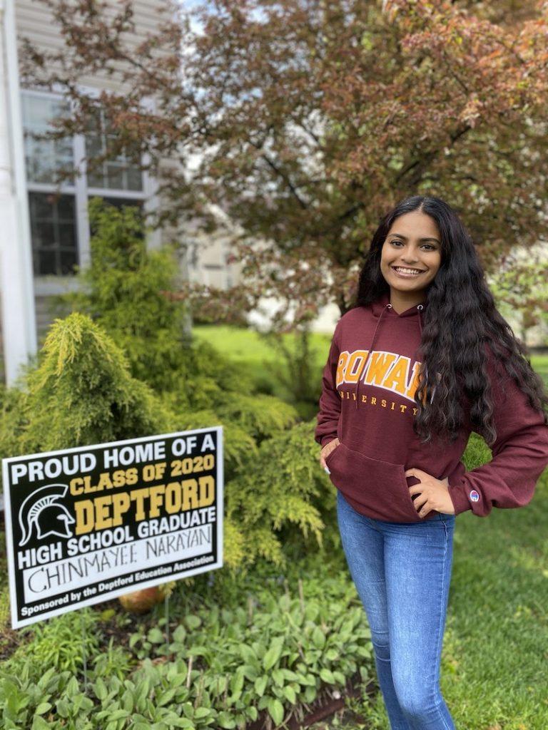 Chinmayee stands in front of a high school graduation sign, wearing a Rowan shirt.