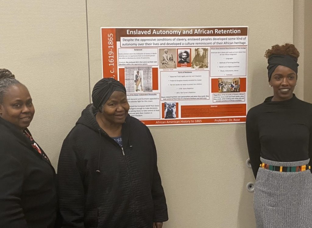 Christine presents her poster with the support of her family.
