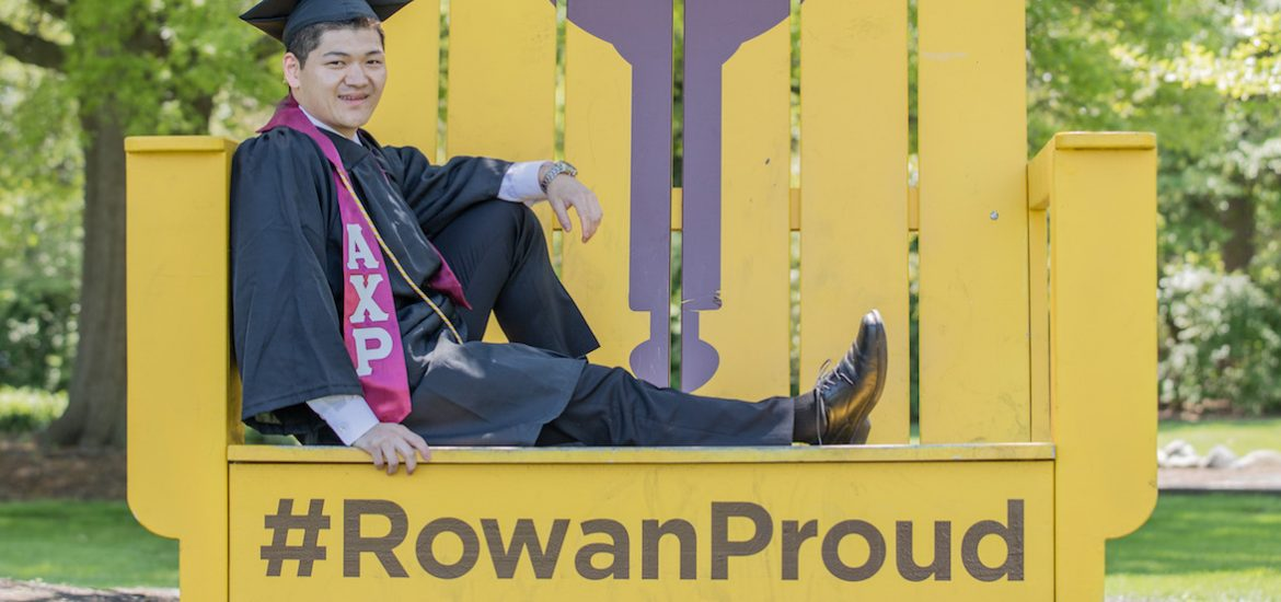 Health promotion and wellness management major Eric Chen posing on the Rowan Proud yellow chair.