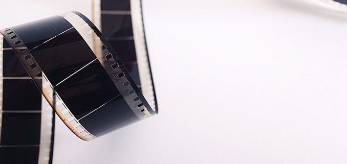 Stock photo of film unrolling against a white background.