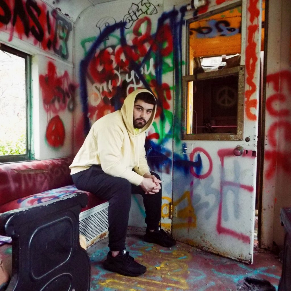 Photo of Frank Ziegler wearing a hooded sweatshirt sitting in a graffiti-covered room