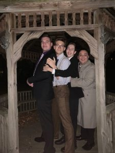 Political science major Jacob poses with three friends under a wooden gazebo.