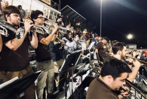 Mike Massaro playing trumpet with a high school band on the bleachers.