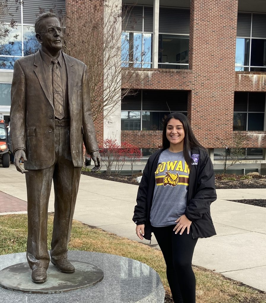 Maria stands in front of a statue of Henry Rowan at Rowan University.