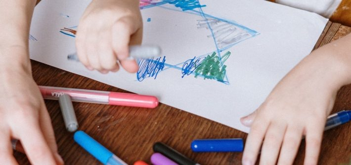 Stock image of close up of adult hands guiding child's hands drawing.