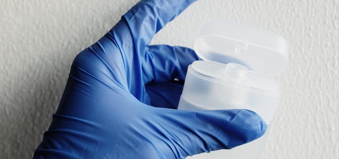 Stock photo of a hand covered with a blue medical glove holding a plastic container.