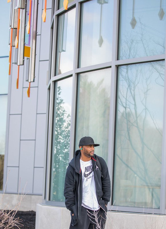 Rasheed stands outside the modern outside of Business Hall, looking off to the side with hands in his pockets.