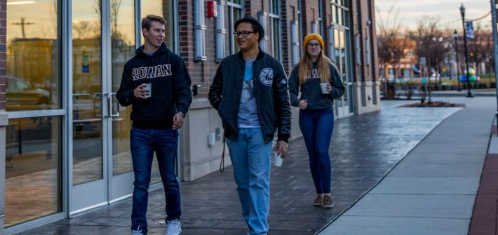 Christian walks down Rowan Boulevard with two other students