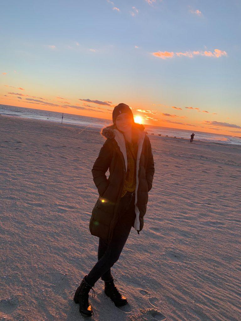 Photo of Bridget on the beach at sunset.