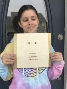 Bri pictured with a photo of a Prof she made out of brail.