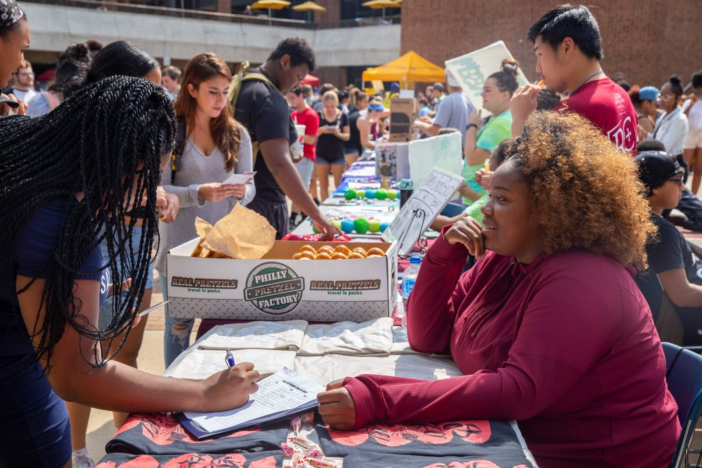 Students outside the Chamberlain Student Center signing up for clubs and organizations at club tables.