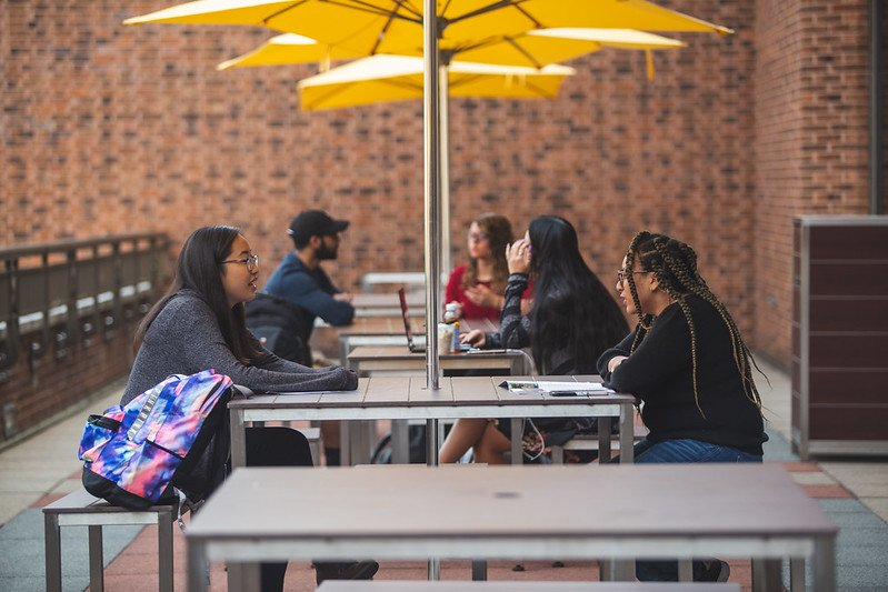 Students sitting at the picnic tables outside above the Student Center Patio.