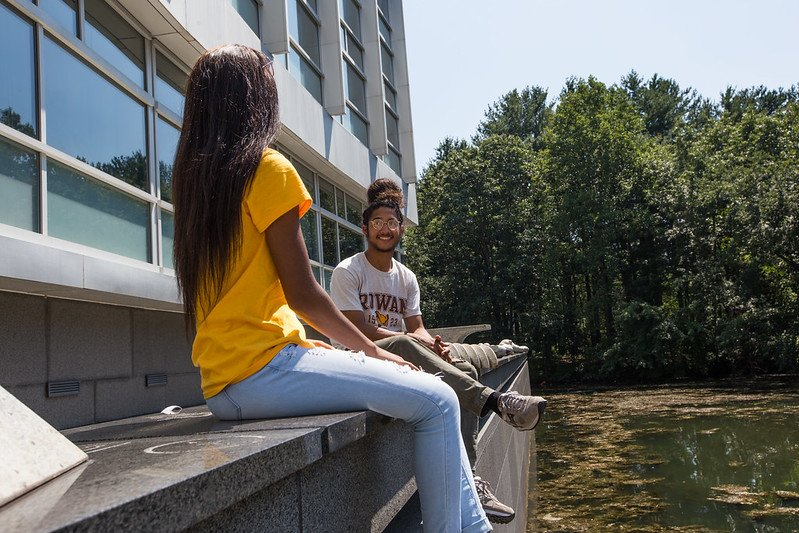Two students wearing Rowan t-shirts sit on a ledge overlooking the Engineering Pond.