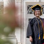 Chelsey Fitton stands in her cap and gown outside of Bunce Hall