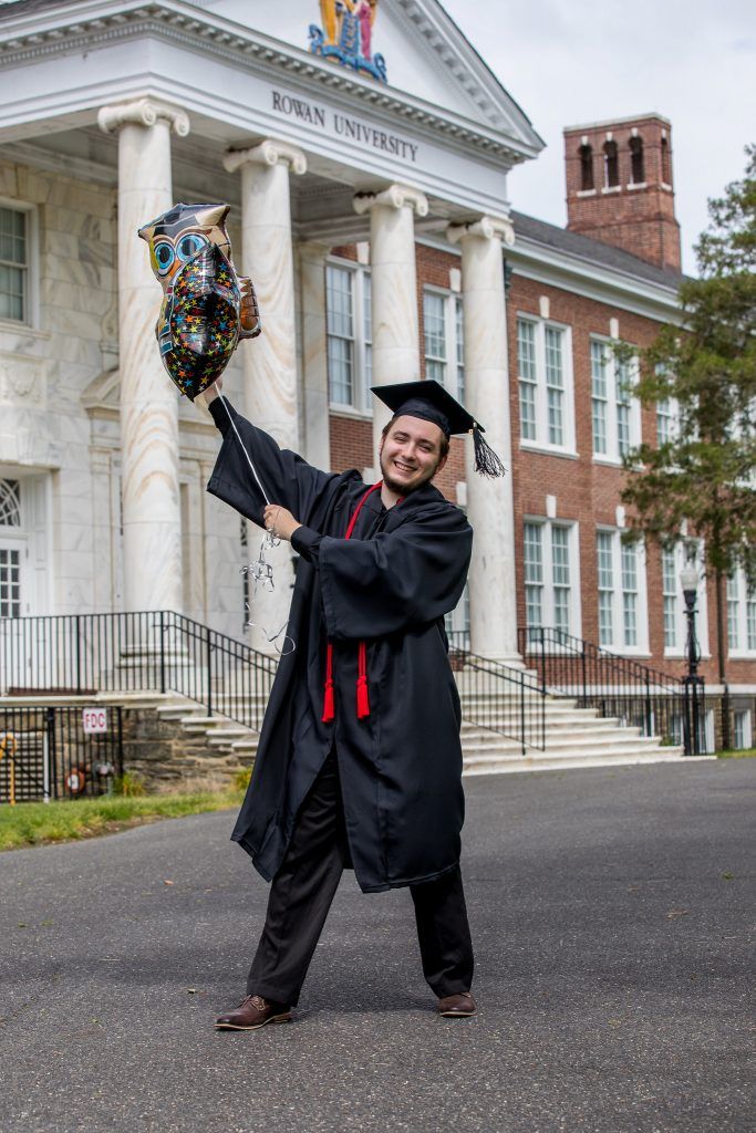 Don holding graduation balloons in front of Bunce Hall