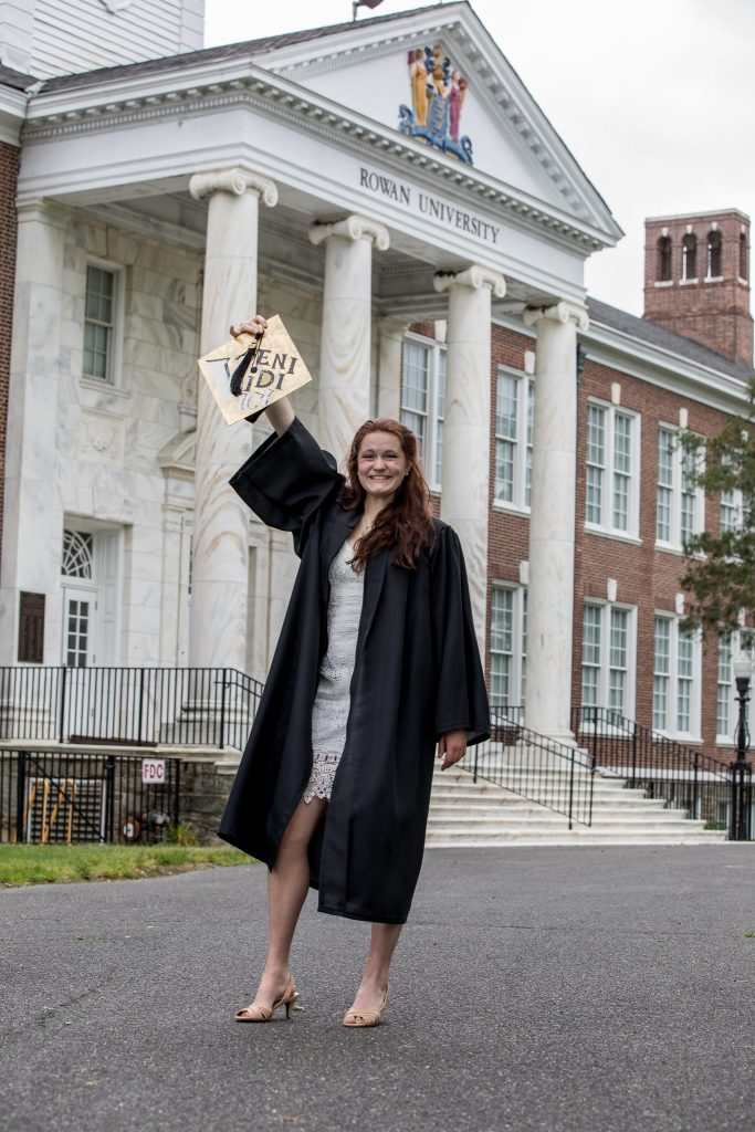 Sarah Transue stands in her graduation gown holding her cap in the air in front of Bunce Hall