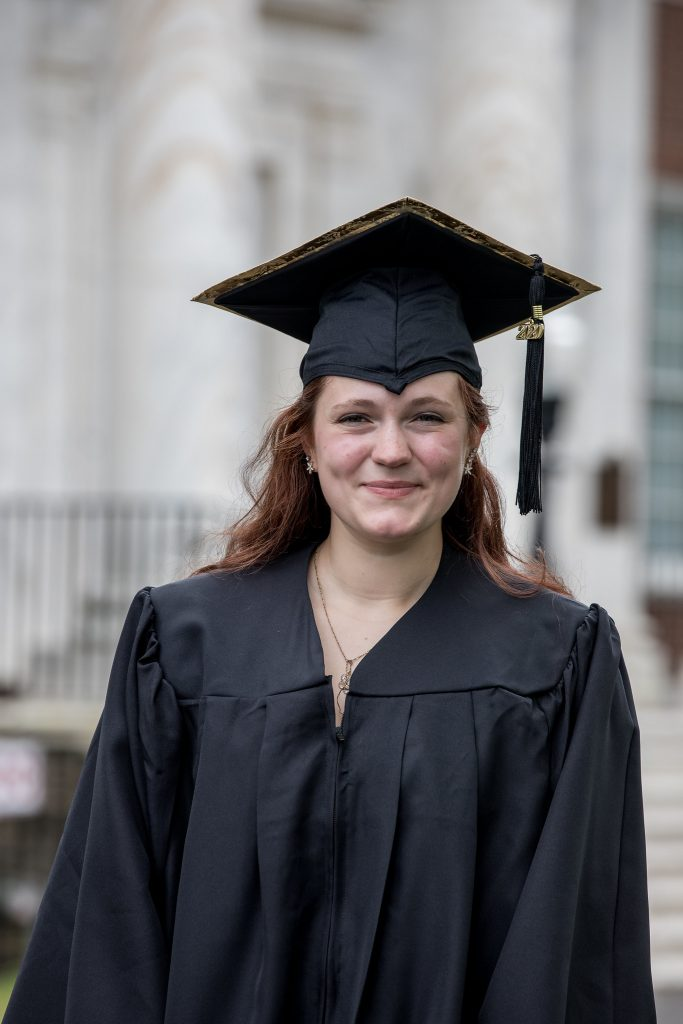 Portrait of Sarah Transue in cap and gown in front of Bunce Hall