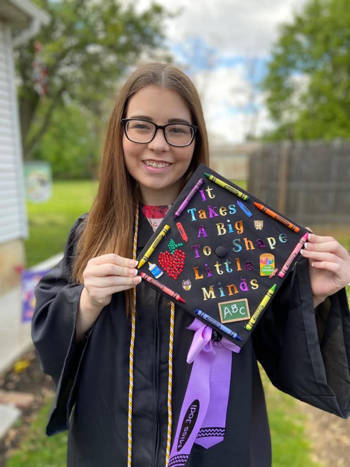 """Jodi holding her decorated Graduation cap that says, """"It takes a big step to shape little minds."""""""