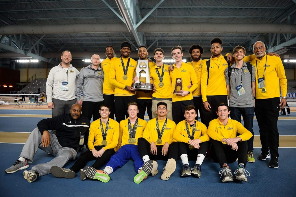 Francis poses with his team with their third place trophy.