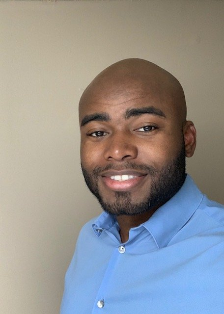 Headshot of Kemet wearing a blue shirt against a neutral background