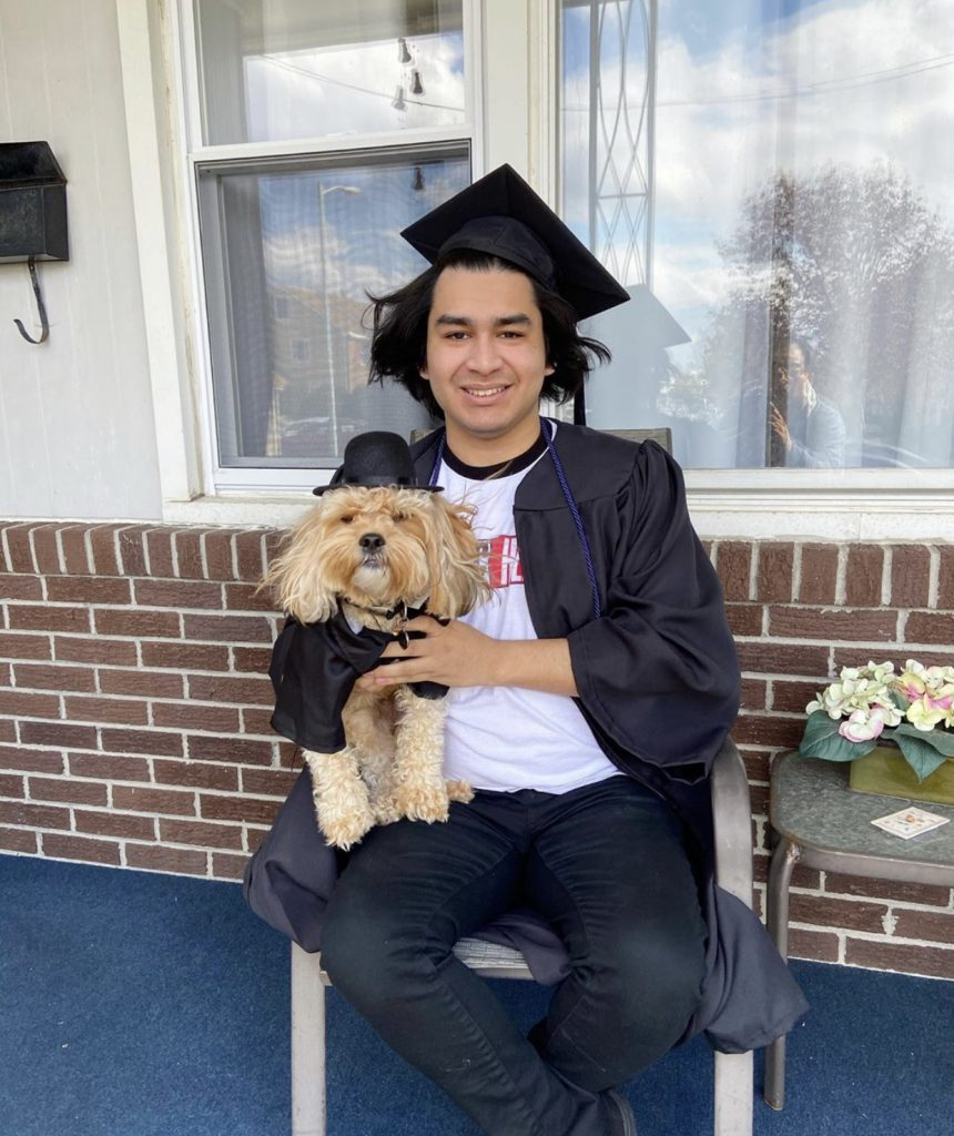 Enzo in his cap and gown sitting on a chair outside a house. He is holding a dog who is wearing a matching cap and gown.