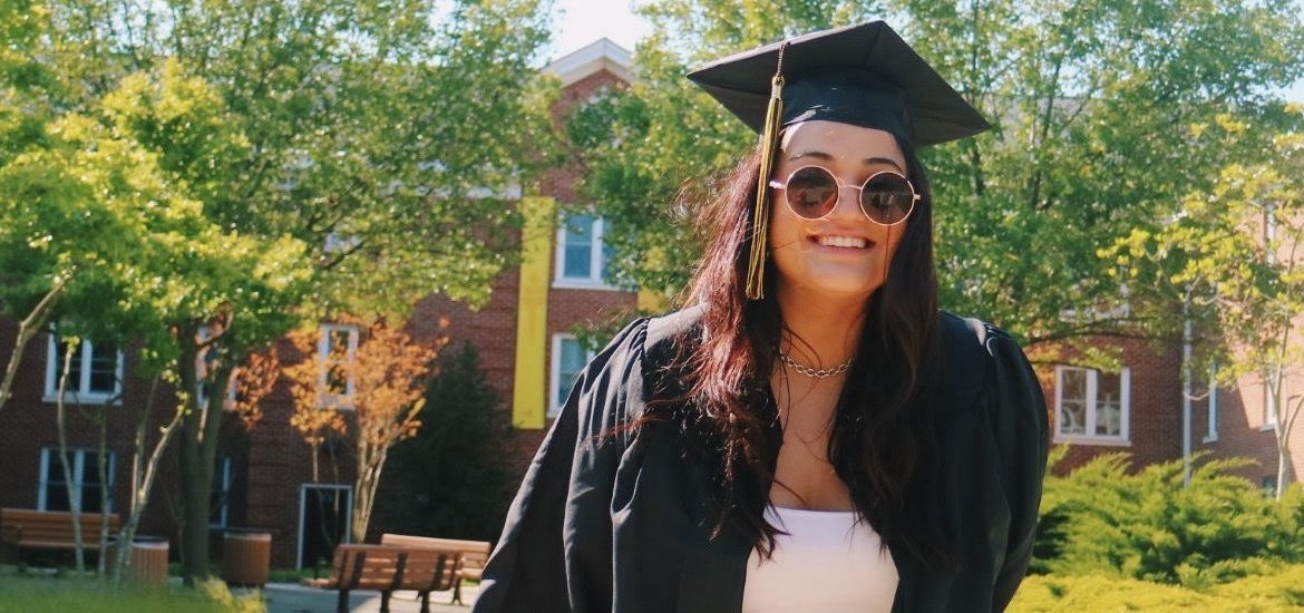 Gianna poses in front of a freshman residence hall in her graduation regalia.