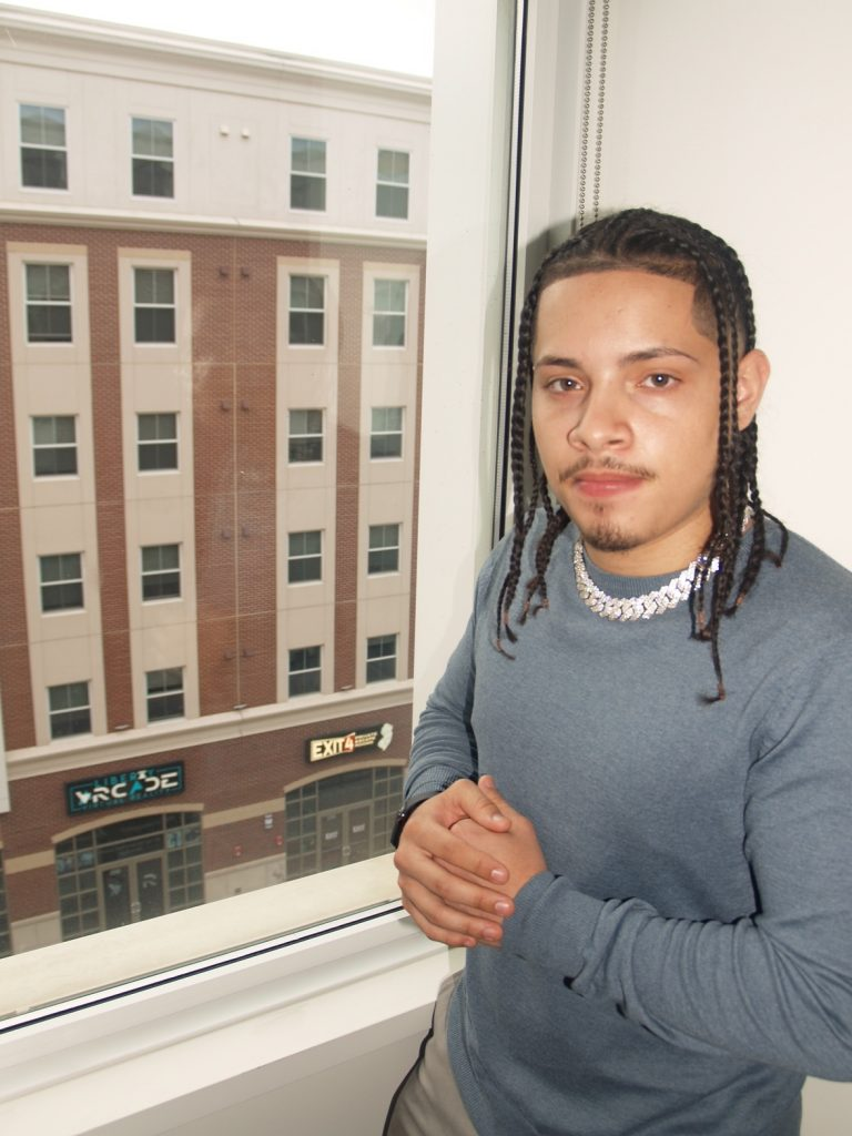 Jeremiah poses next to a window overlooking Rowan Boulevard.