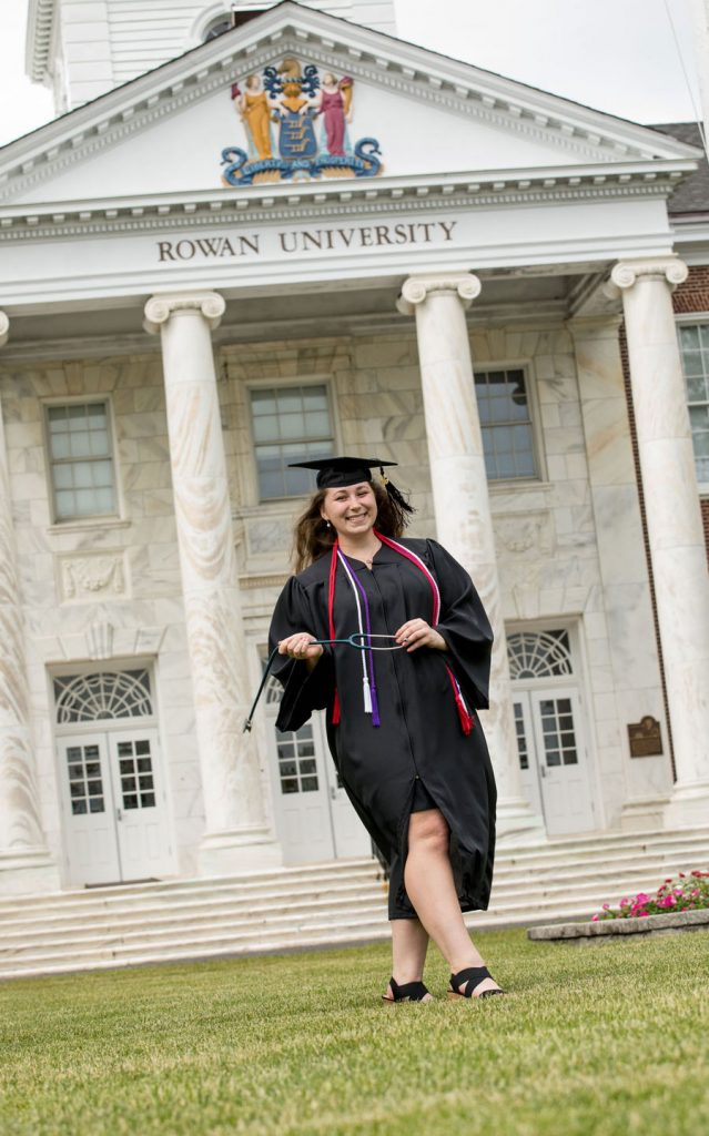 Kira walks down Bunce Green in her cap and gown