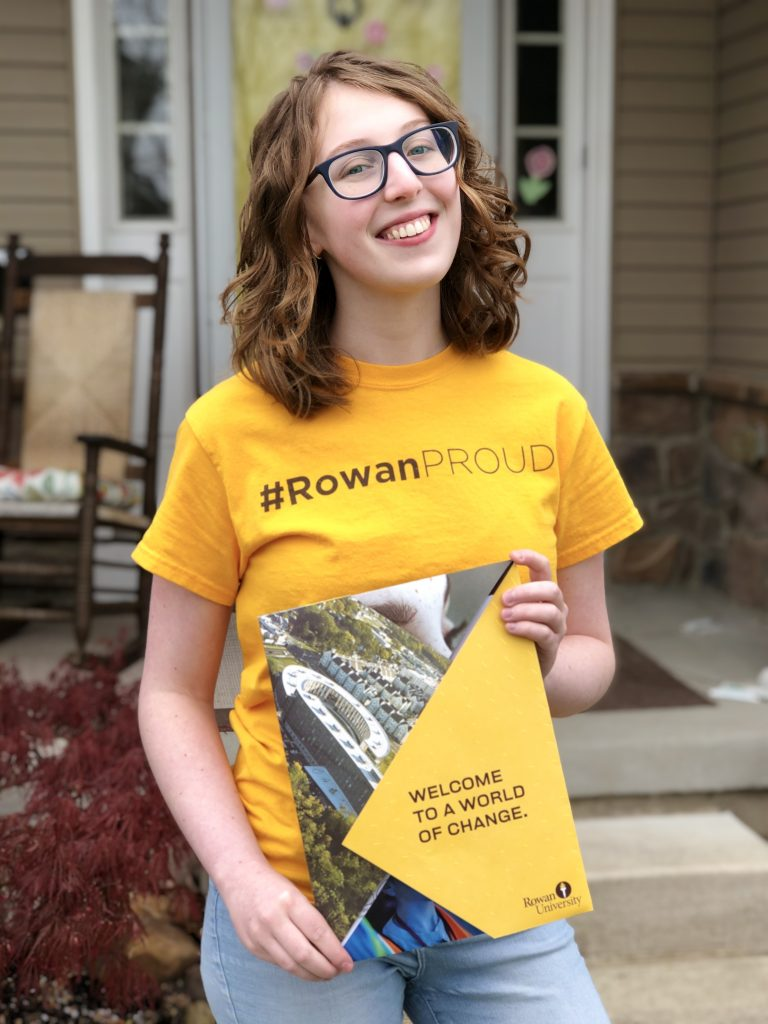 Emma poses outside her home wearing a #RowanPROUD t-shirt and holding her acceptance letter.