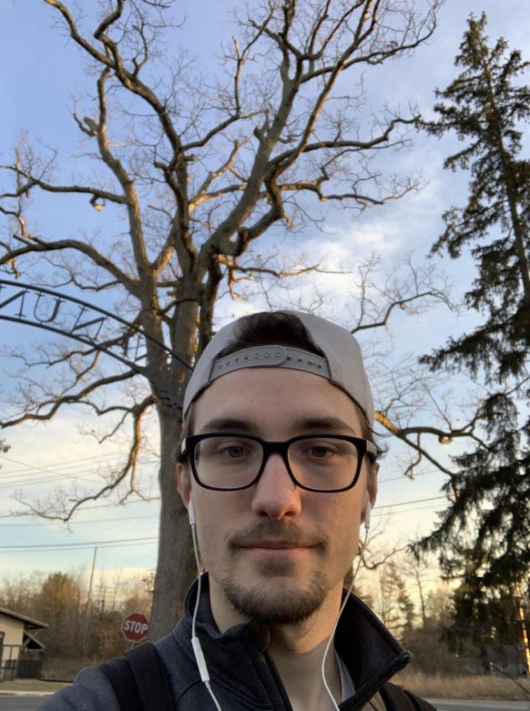 Matthew takes a selfie outdoors.