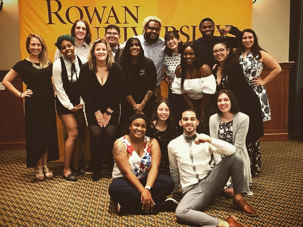 "Dominique poses with some friends in front of a ""Rowan University"" banner."