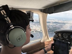 Mechanical engineering major Jay flying a plane over New York City.