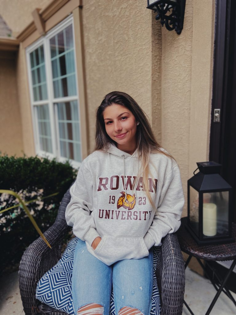 Julia sitting and smiling wearing a Rowan sweatshirt.