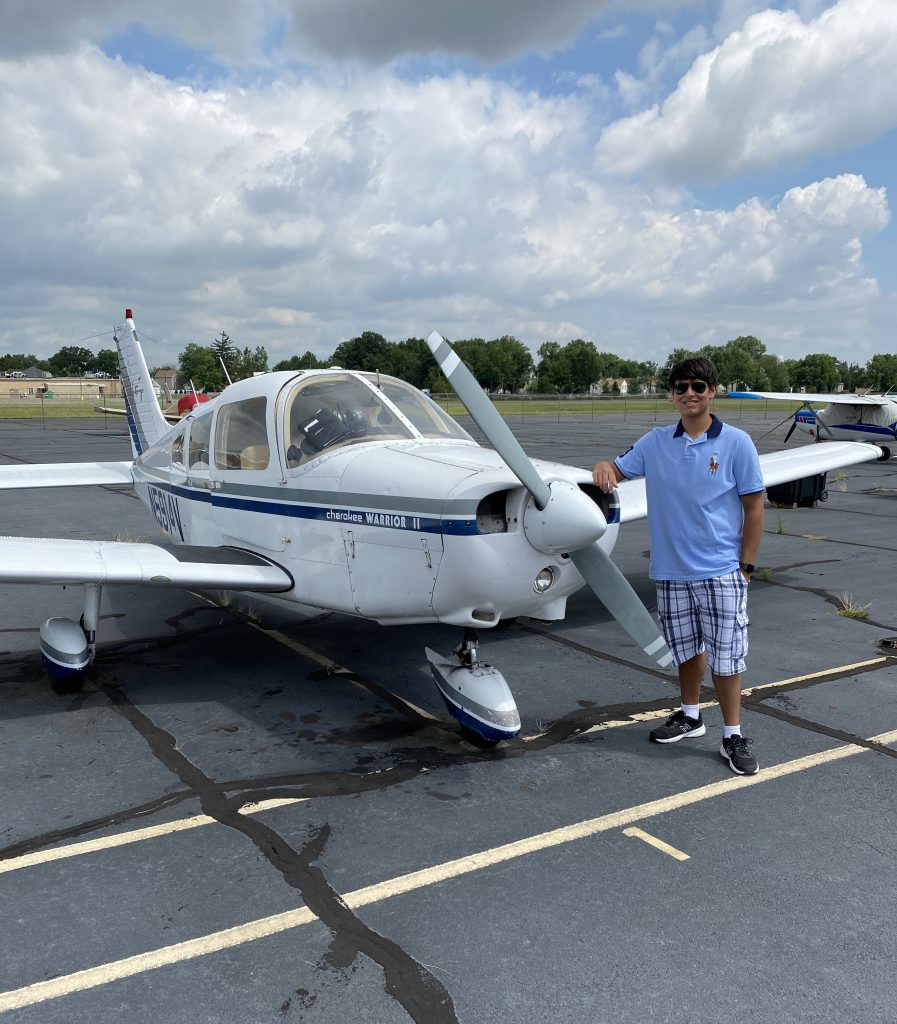 Jay posing next to a small private plane.