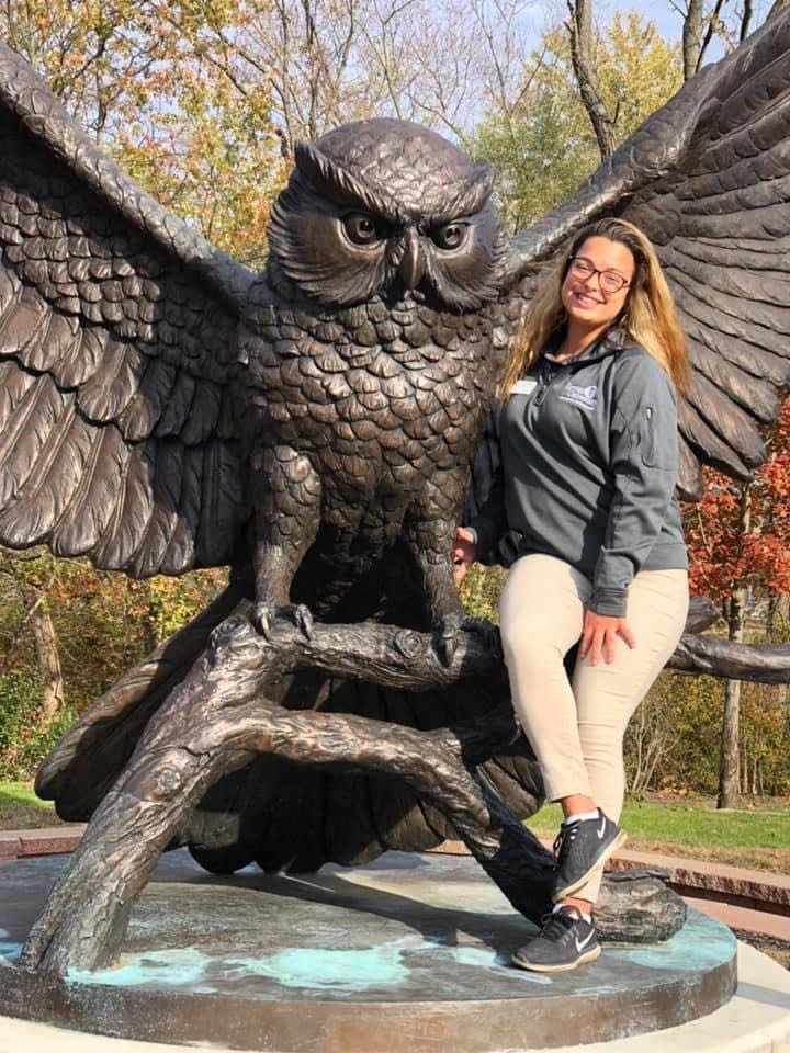 Psychology major Callie poses with the Rowan owl statue.