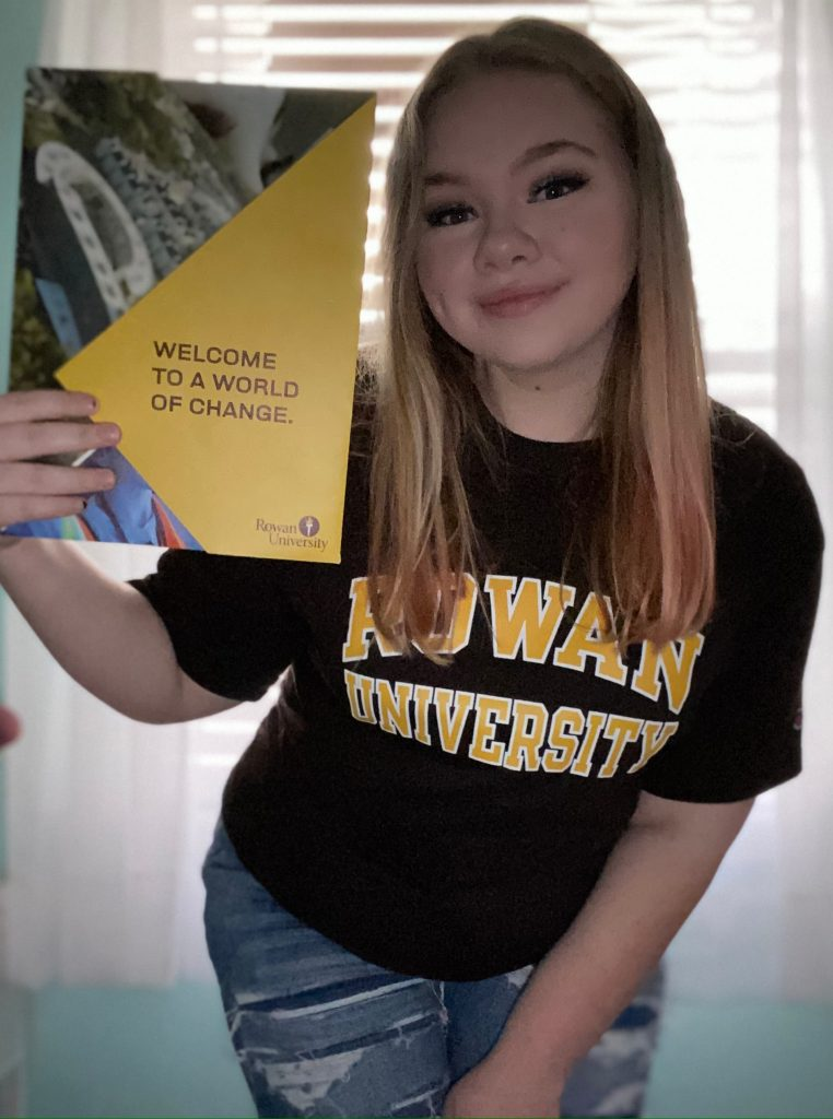 Morgan pictured in Rowan apparel with her admissions acceptance packet
