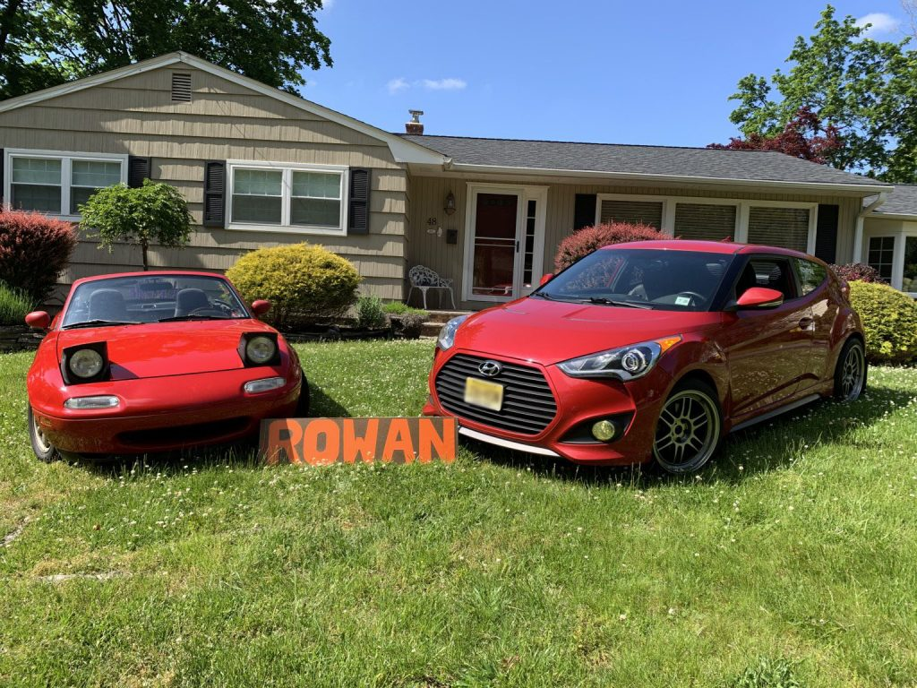 Photo of AJ Marchev's cars and Rowan sign outside his home.