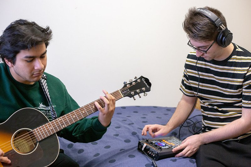 Two roommates create music in their living space