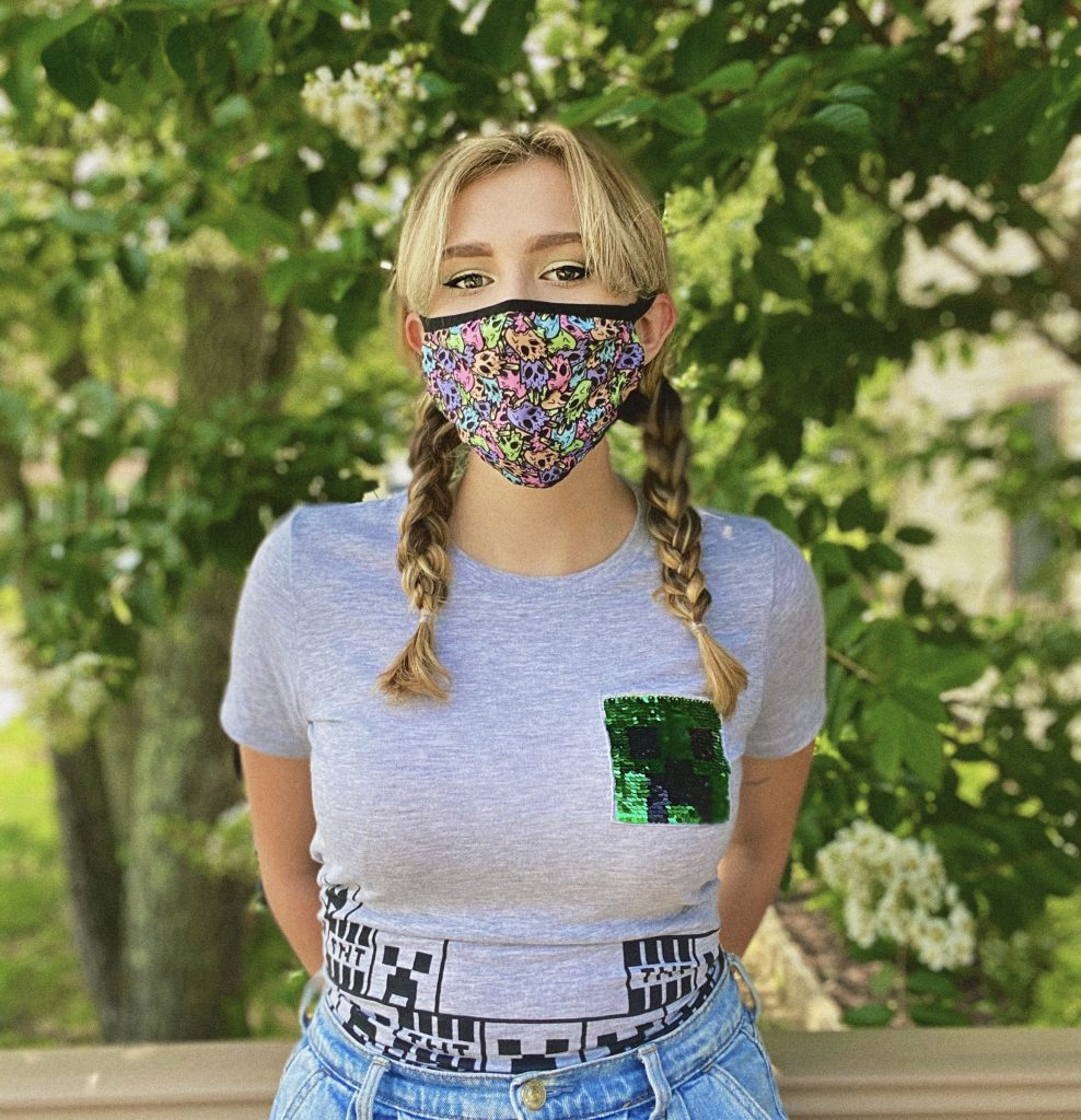 Biology major Jill Taylor wears her favorite web series mask and stands outside