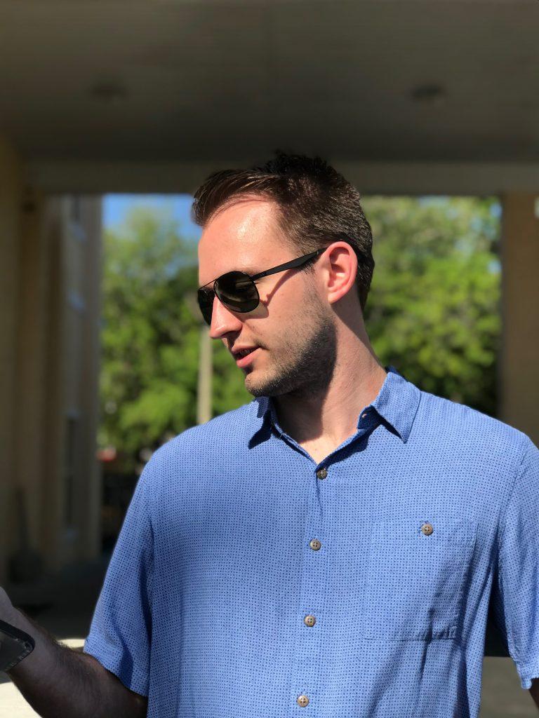 Joseph Breymeier standing in sunlight looking down at his phone.