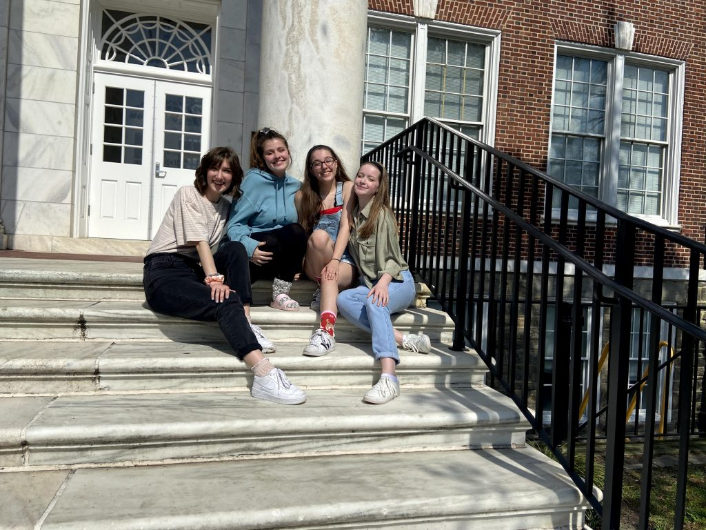 Erica sitting with friends on the Bunce Hall steps.